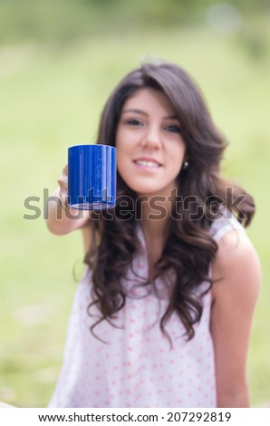portrait of beautiful young girl holding a cup of coffee in a field selective focus - stock photo