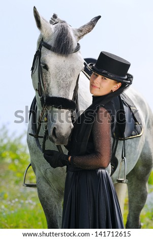 Portrait of beautiful young girl in black dress  with horse - stock photo