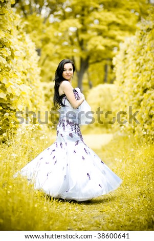 Portrait of beautiful young girl in elegant white dress on autumn park - stock photo
