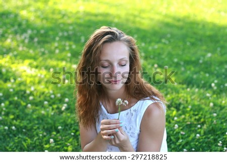 Portrait of beautiful young girl in the green park