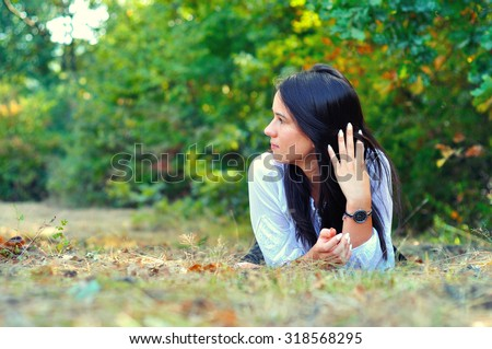 Portrait of beautiful young girl laying on grass