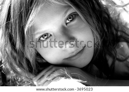 portrait of beautiful young girl lying in the rays of sun - stock photo