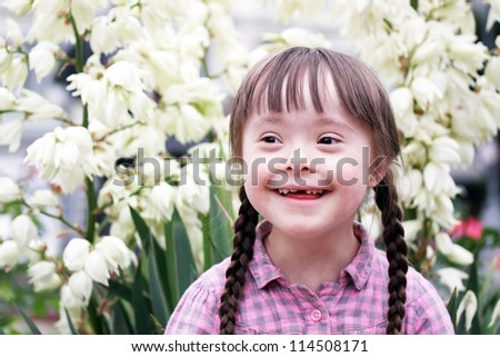 Portrait of beautiful young girl on flowers background. - stock photo