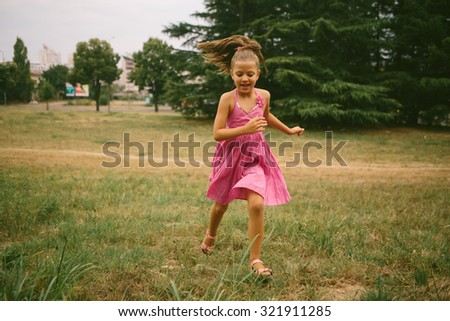 Portrait of beautiful young girl running at the park - stock photo