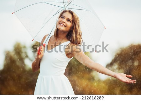 Portrait of beautiful young girl walking with umbrella under rain - stock photo