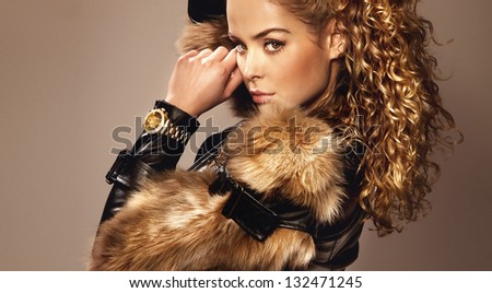 Portrait of beautiful young girl wearing fashionable fur and watch, looking at camera. - stock photo
