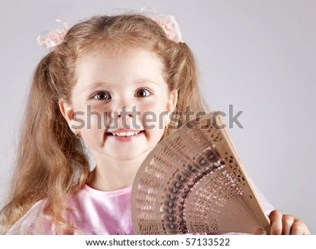Portrait of beautiful young girl with fan - stock photo