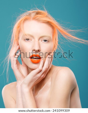 Portrait of beautiful young girl with orange hair on a blue background, surprise - stock photo