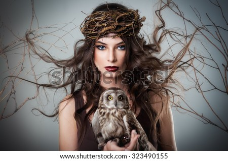 Portrait of beautiful young girl with owl  - stock photo