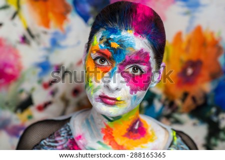 Portrait of beautiful young girl, woman, lady,model,painting, canvas, crazy art, painting,expressionism. Bright creative makeup, expressive eyes, paint, colorful, yellow, blue, pink, white flowers.  - stock photo