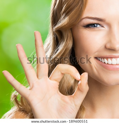 Portrait of beautiful young happy smiling blond woman with okay gesture, outdoors