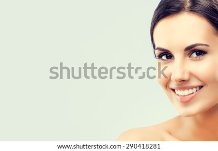 Portrait of beautiful young happy smiling brunette woman, with naked shoulders, with empty blank copyspace area for slogan or text - stock photo