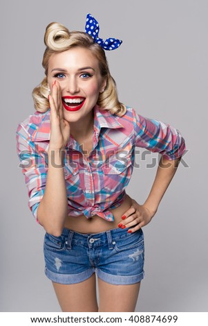 Portrait of beautiful young happy smiling woman, dressed in pin-up style. Caucasian blond model posing in retro fashion and vintage concept studio shoot, on grey background. - stock photo