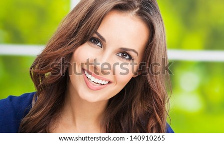 Portrait of beautiful young happy smiling woman, outdoors - stock photo
