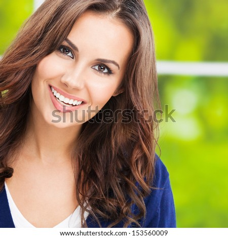 Portrait of beautiful young happy smiling woman, outdoors, with copyspace - stock photo