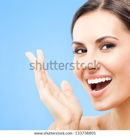 Portrait of beautiful young happy smiling woman, over blue background - stock photo