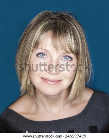 Portrait of beautiful young happy smiling woman, over blue background. Portrait of a smiling middle aged caucasian woman - stock photo