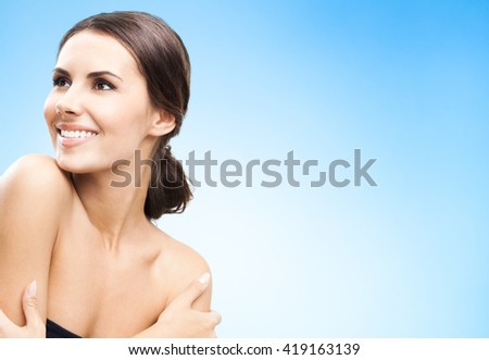 Portrait of beautiful young happy smiling woman, over blue background, with copyspace for slogan or text message - stock photo