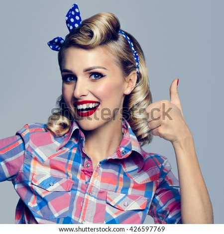 Portrait of beautiful young happy smiling woman, showing thumb up gesture, dressed in pin-up style. Caucasian blond model posing in retro fashion and vintage concept studio shoot. - stock photo