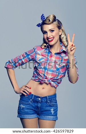 Portrait of beautiful young happy smiling woman, showing two fingers or victory gesture, dressed in pin-up style. Caucasian blond model posing in retro fashion and vintage concept studio shoot.