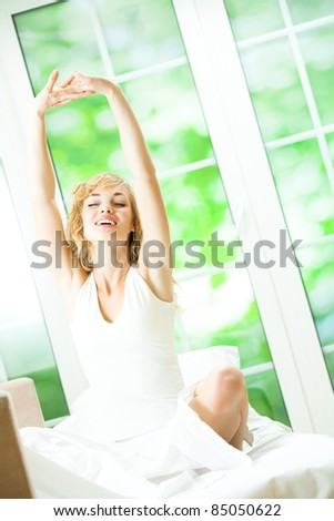 Portrait of beautiful young happy smiling woman waking up at bedroom - stock photo