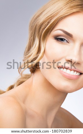 Portrait of beautiful young happy smiling woman with blond hair, over grey background