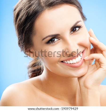 Portrait of beautiful young happy smiling woman with long curly hair, over blue background - stock photo