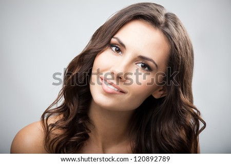 Portrait of beautiful young happy smiling woman with long curly hair, over grey background - stock photo