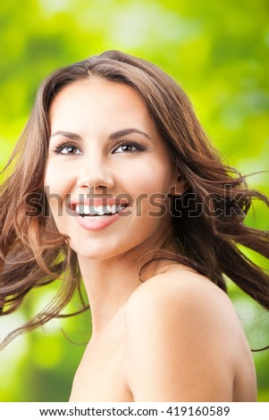 Portrait of beautiful young happy smiling woman with long hair, outdoors - stock photo