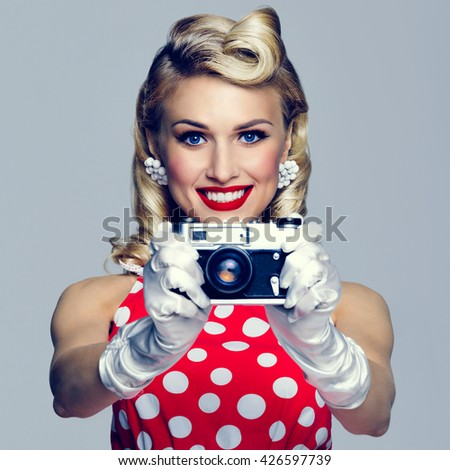 Portrait of beautiful young happy smiling woman, with no-name old film camera, taking picture, dressed in pin-up style. Caucasian blond model posing in retro fashion and vintage concept studio shoot. - stock photo