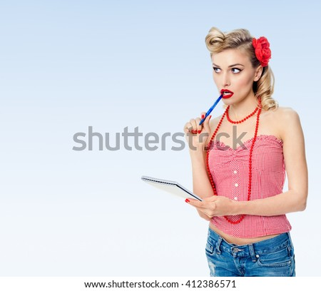Portrait of beautiful young happy smiling woman with notepad, in pin-up style clothing, on blue background, with blank copyspace area for text or slogan - stock photo