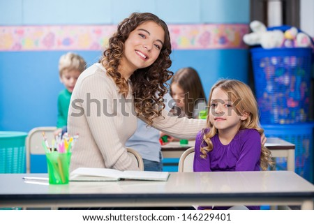 Portrait of beautiful young kindergarten teacher with arm around little girl in classroom - stock photo