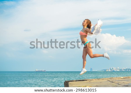 Portrait of beautiful young lady having fun in high jump over outdoors copy space background - stock photo