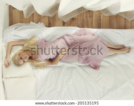 Portrait of beautiful young lady in bedroom. Top view
