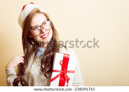 portrait of beautiful young lady in Santa red hat and glasses holding gift box - stock photo