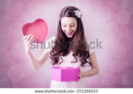 Portrait of beautiful young lady looking at love heart gift box on bokeh lights copy space background - stock photo