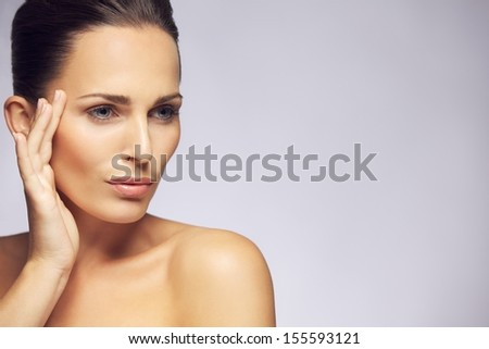 Portrait of beautiful young lady pampering her clean and fresh face skin and looking away at copy space against gray background. Pretty young female model touching her healthy and perfect skin. - stock photo