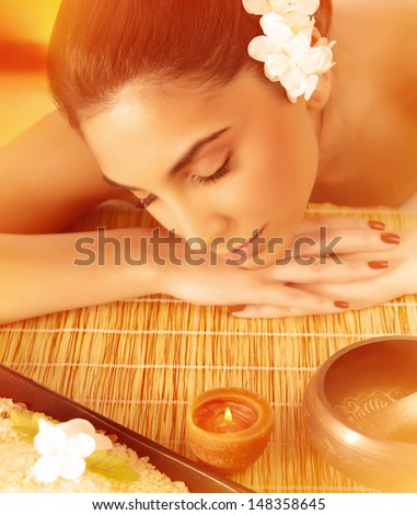 Portrait of beautiful young lady sleeping on massage table outdoors, day spa on the beach resort, orange sunset light, pleasure concept  - stock photo