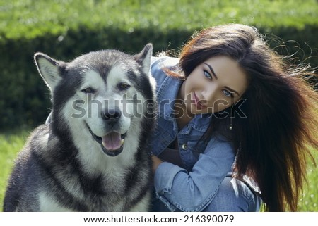 Portrait of beautiful young lady with blue eyes, long hair and wearing blue jeans, posing with big Alaskan Malamute male dog in summer sunlight. - stock photo
