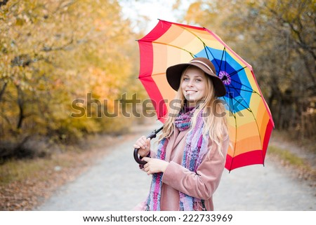 portrait of beautiful young lady with rainbow colorful umbrella having fun happy smiling and looking at camera over autumn road against light sky copy space background - stock photo