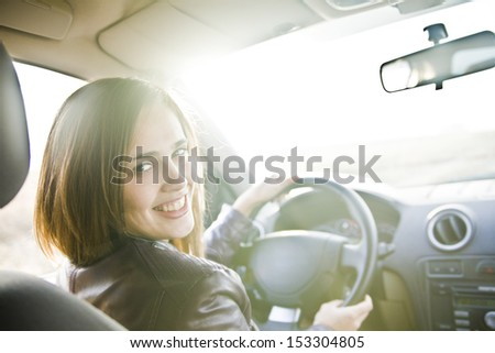 Portrait of beautiful young latin hispanic brunette woman in the new car - indoor keeps the wheel turning around and smiling and looking at the passengers in back seat. The idea of  taxi driver - stock photo