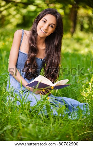 portrait of beautiful young long-haired brunette woman in dress holding book and smiling in park - stock photo