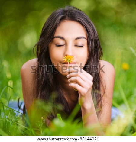portrait of beautiful young long-haired woman lying in park and smelling flowers - stock photo