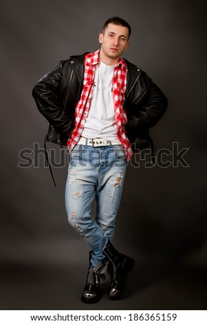 portrait of beautiful young man in a leather jacket on a gray background shot in studio - stock photo
