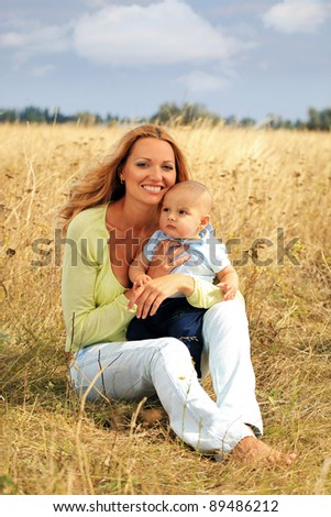 Portrait of beautiful young mother and at her baby outdoors - stock photo