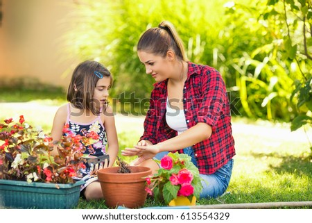 Portrait of beautiful young mother and daughter gardening together in front or back yard