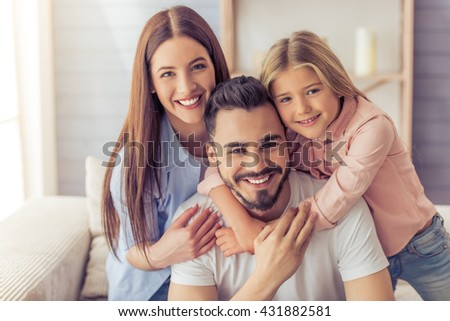 Portrait of beautiful young mother, father and their daughter hugging, looking at camera and smiling while sitting on sofa at home