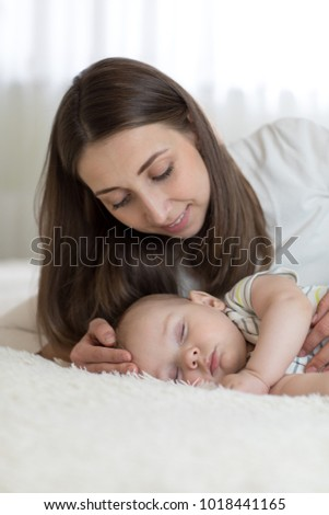 Portrait of beautiful young mother with her 7 months old baby sleeping in the bed