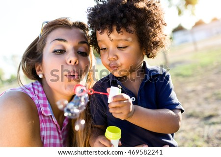 Portrait of beautiful young mother with her son blowing soap bubbles in the park.