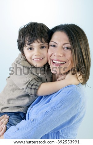 Portrait of beautiful young mother with his son sitting cheek to cheek, smiling and happy against blue background. - stock photo
